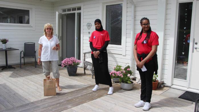 Torslandabon Lena Lomande r får sin bokkasse levererad av Sadia Abdi och Heron Gebreyesus. Foto: Biblioteken i Västra Hisingen
